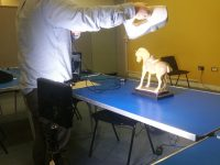 Developer with a 3D scanner is photographing the Tang Dynasty Horse on a blue table