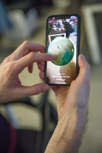 Civilisations AR demonstartion image, man holding touchscreen phone with image of augmented reality globe